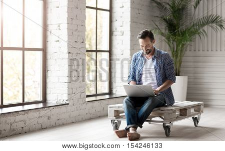 Interactive communication. Nice attractive joyful man holding a laptop and having an online chat with somebody while sitting in the room