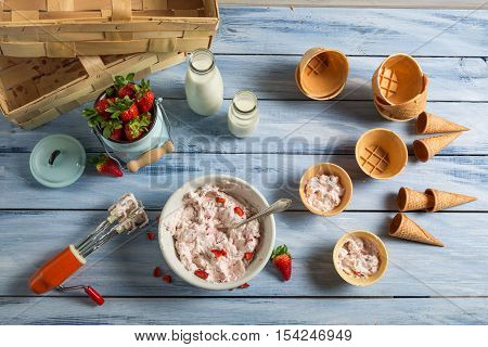 Preparing homemade fruit ice cream on wooden table
