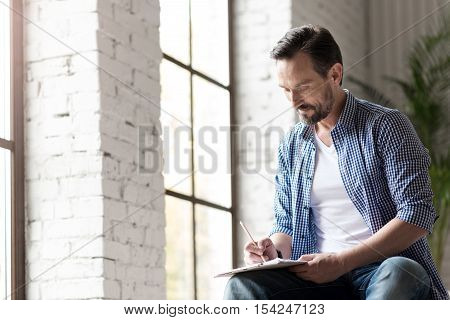 Favourite hobby. Good looking delighted talented man sitting near the window and holding a pencil while drawing a picture