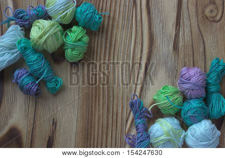 Many small multicolor melange cotton yarn balls for knitting crochet on wooden rustic background backdrop