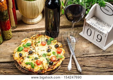 Freshly pizza served with red wine on wooden table