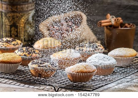 Falling powder sugar on vanilla muffins on wooden table