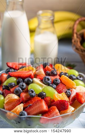 Preparing a healthy fruit salad on wooden table