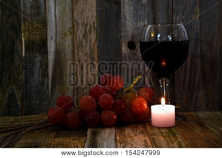 red wine in glass with grapes and glowing candle on rustic wood