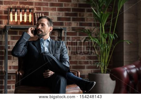 Involved in the discussion. Good looking attractive confident man sitting in an armchair and listening attentively to his interlocutor while having a conversation