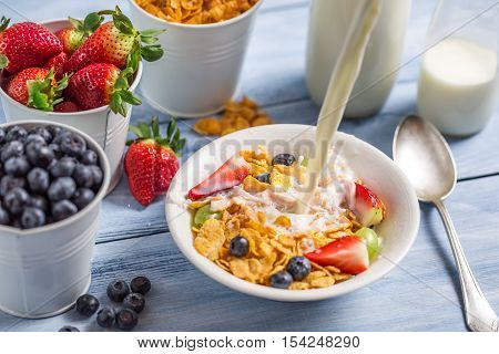 Pouring milk into cornflakes with fruits on wooden table