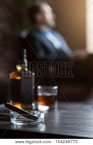 For true men. Selective focus of a cigar lying in the ashtray near the whisky bottle with a handsome nice confident businessman sitting in the background