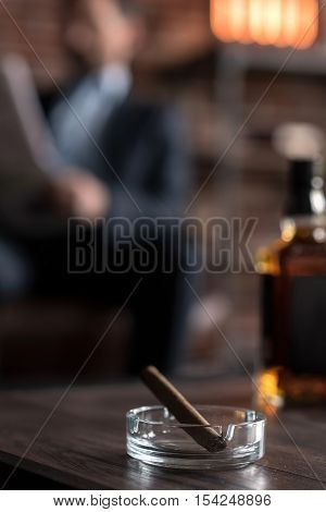 Bad habit. Selective focus of a cigar lying in the ashtray near the bottle of whisky with a nice successful confident businessman reading a newspaper in the background