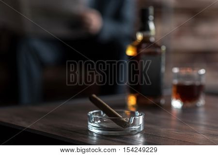 Smoking habits. Selective focus of a cigar lying in the ashtray next to the bottle of whisky with a hard working confident successful businessman sitting in the background