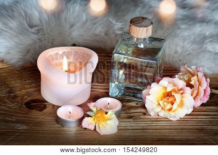Spa decoration with aromatic oil and candle on a wooden table with lambskin