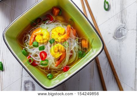 Thai soup with noodles and shrimp on wooden table