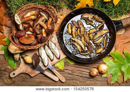 Preparing wild mushrooms to frying on wooden table