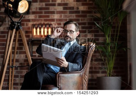 Bad eyesight. Nice serious adult man sitting in the armchair and holding his glasses while reading his notes