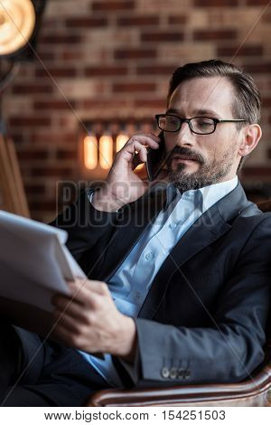Business talk. Nice handsome stylish businessman holding some documents and looking at them while talking on the phone