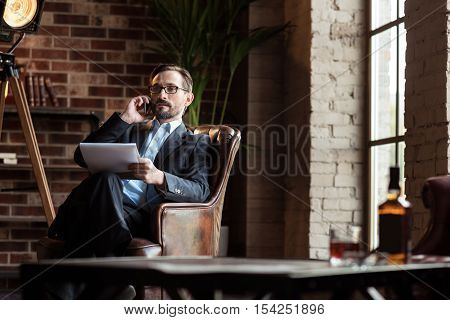 Work conversation. Handsome stylish calm businessman wearing an expensive suit and speaking on the cell phone while working in his study