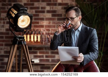 Expensive alcohol. Handsome serious stylish man standing near the armchair and taking a sip of whisky while reading his notes