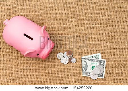 Pile Of Loose Usd Cash Feeding A Piggy Bank