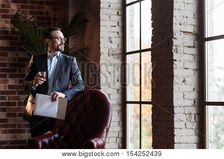 View from the study room. Pleasant handsome confident man standing near the window and looking into it while holding a glass of whisky
