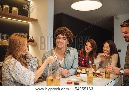 Woman feeding her boyfriend with junk food.