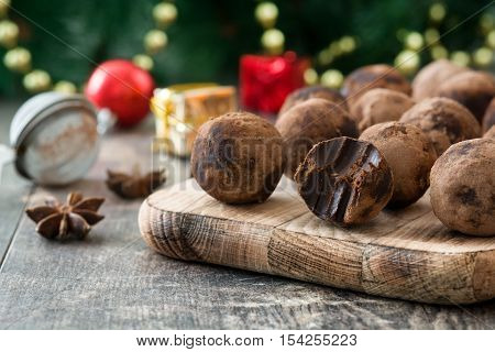 Christmas chocolate truffles and Christmas decoration on wooden table