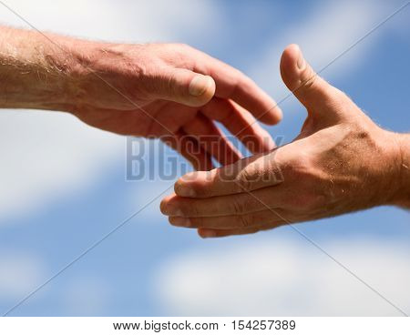 Two hands reaching out to each other against sky poster