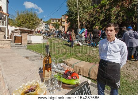 TBILISI, GEORGIA - OCT 16, 2016: Young man invites tourists for tasting Chacha traditional alcoholic drink at city festival Tbilisoba on October 16, 2016. Tbilisoba is a festival in Tbilisi from 1979