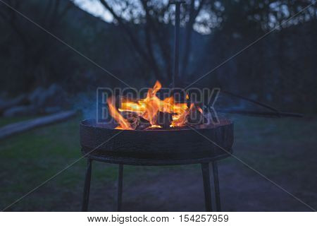 Burning camp fire at dusk in camping site preparing for barbeque or braai outdoors activity in South Africa. Selective focus on fire and firewood very shallow depth of field cold toned image.