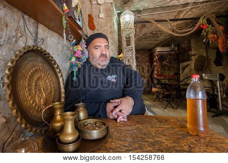 TBILISI, GEORGIA - OCT 16, 2016: Elderly man with bottle of homemade white wine sitting in wine bar at historical stone cellar on October 16, 2016. Tbilisi has a population of 1.5 million people