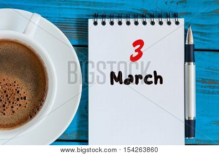 March 3rd. Day 3 of month, calendar on blue wooden table background with morning coffee cup. Spring time, Top view.