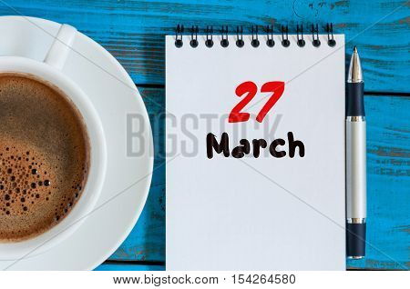 March 27th. Day 27 of month, calendar on blue wooden table background with morning coffee cup. Spring time, Top view. World Theatre Days.