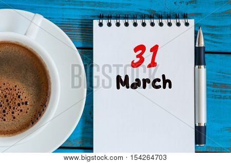 March 31st. Day 31 of month, calendar on blue wooden table background with morning coffee cup. Spring time, Top view.