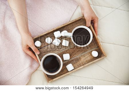 bed tray with coffee and marshmallows. female hands put a wooden tray for breakfast with two cups of coffee and sweets on the bed