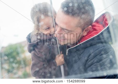 Young father holding his little daughter under the transparent umbrella in town on a rainy day.