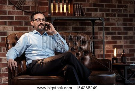 Distance communication. Handsome delighted good looking businessman putting the smartphone to his ear and listening to his interlocutor while being in his study room