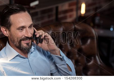 Pleasant conversation. Positive cheerful bearded man listening to his interlocutor and laughing while having a pleasant conversation on the phone