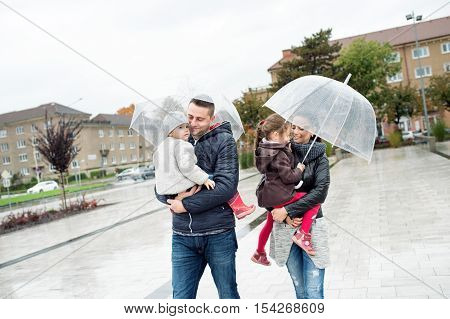 Beautiful young family with two little daughters under the umbrellas, in town on a rainy day.