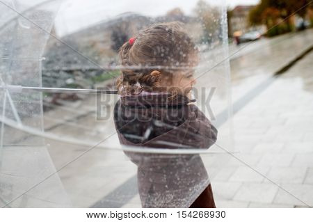 Cute little girl under the transparent umbrella in town on a rainy day, rear view.