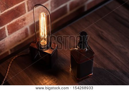 Decoration for a male study room. Close of a shining small decorative lamp standing on the floor near the bottle of whisky
