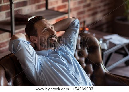 Feeling great. Positive happy bearded businessman sitting on the sofa and putting hands behind his head while enjoying his relaxation