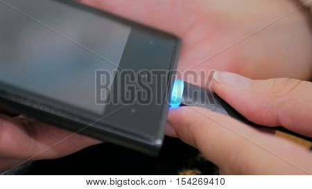 Woman's hand plugging black lightning charging cable into smartphone - USB data cable connecting on modern gadget. Close up