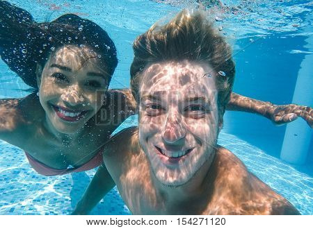 happy couple underwater. Smiling boy and girl making selfie in the swimming pool