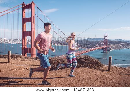 Couple running in San francisco. Golden gate bridge in the background