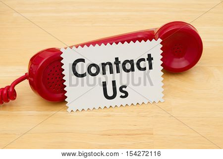 How to contact us A retro red phone with note card on a desk with text Contact Us
