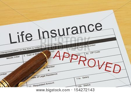 Applying for a Life Insurance Approved Life Insurance application form with a pen on a desk with an approved stamp