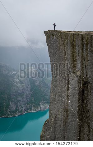 Tourist with backpack is standing at the cliff of famous norwegian touristic attraction - Prekestolen rock. Vertical photo, Lysefjord, Rogaland, Norway.
