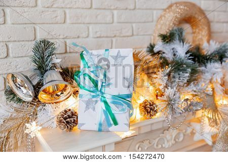 Christmas and New Year decorations on mantelpiece. Holiday winter background with wrapped present. Gift with paper bow.