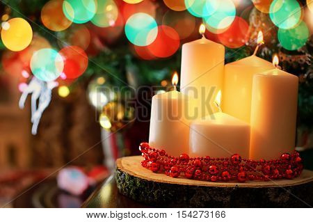 set of white candles of different sizes in the background dressed up Christmas tree