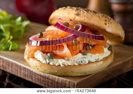 A delicious toasted bagel with smoked salmon cream cheese capers and red onion.