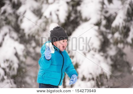 Cute little boy in blue jacket and hat playing outside in winter nature, throwing snow balls
