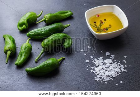 Food and drink, still life, moody concept. Raw green peppers pimientos de padron mexican jalapeno spanish tapas olive oil sea salt on a wooden table. Selective focus